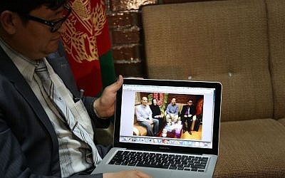"""Mohammad Hadi Hadayati, Kabul University's vice chancellor shows a photograph, from left, slain American Jon Gabel, his mother, his father Gary Gabel, who was also killed, and himself, during an interview with the Associated Press in Kabul, Afghanistan, Saturday, April 26, 2014. An Afghan police security guard opened fire on foreigners, on Thursday, April 24, 2014, as they entered the grounds of Cure International Hospital, killing three people, including pediatrician Dr. Jerry Umanos of Chicago. On Saturday, Kabul University vice chancellor Mohammad Hadi Hadayati identified the other two Americans killed in the attack as health clinic administrator Jon Gabel and his visiting father, Gary, also from the Chicago area. Jon Gabel's wife, also an American, was wounded, Hadayati said. """"We have lost a great man, a great teacher, a man who was here only to serve the Afghan people,"""" Hadayati said. Jon Gabel worked for the U.S.-based charity Morning Star Development and ran a health clinic at Kabul University, teaching computer science classes in his spare time, Hadayati said. Jon Gabel's parents were visiting from Chicago, and Hadayati had lunch with the whole family the day before the attack. (photo credit: AP photo/Rahmat Gul)"""