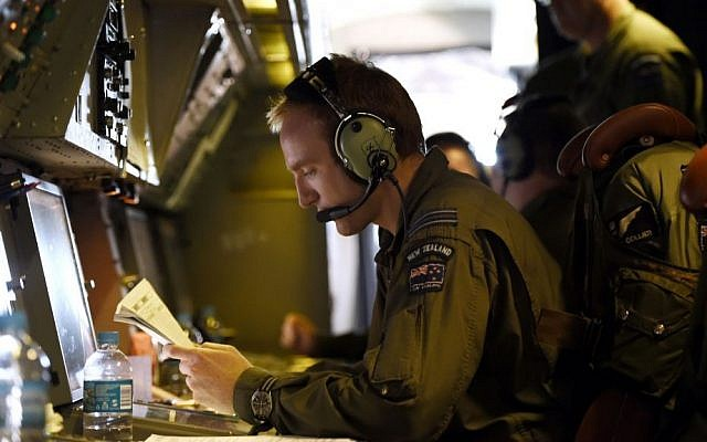 Flight Lieutenant Stephen Graham studies notes aboard a Royal New Zealand Air Force (RNZAF) P-3 Orion on route to search over the southern Indian Ocean looking for debris from missing Malaysia Airlines flight MH370 Friday, April 11, 2014. (AP Photo/Richard Polden)