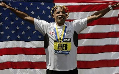 Meb Keflezighi, of San Diego, California, celebrates his victory with an American flag after the 118th Boston Marathon, on Monday, April 21, 2014 (photo credit: AP/Charles Krupa)