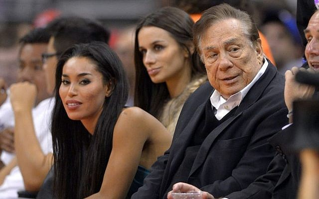 Los Angeles Clippers owner Donald Sterling, right, and V. Stiviano, left, watch the Clippers play the Sacramento Kings in Los Angeles in October, 2013.  (photo credit: AP/Mark J. Terrill)