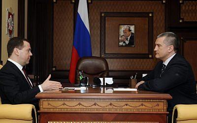 Russian Prime Minister Dmitry Medvedev, left, speaks to Crimean Premier Sergei Aksyonov while visiting Crimea in Simferopol, Crimea, Monday, March 31, 2014. (AP Photo/Alexandr Polegenko)