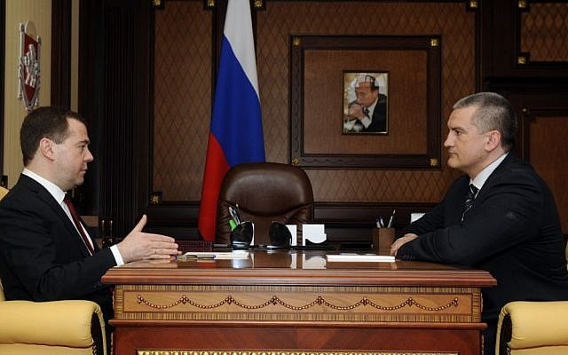 Russian Prime Minister Dmitry Medvedev, left, speaks to Crimean Premier Sergei Aksyonov while visiting Crimea in Simferopol, Crimea, Monday, March 31, 2014. (AP Photo/Alexandr Polegenko)