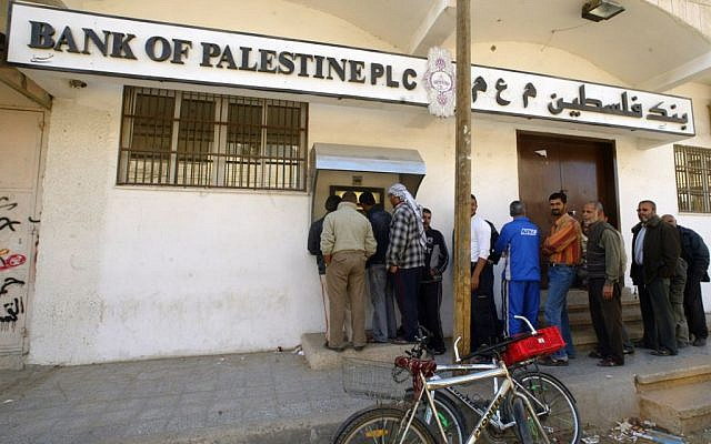 Crowds of Palestinians wait to draw money from an automated teller machine (ATM) of the Bank of Palestine, December 12, 2008. (photo credit:Abed Rahim Khatib / Flash90)