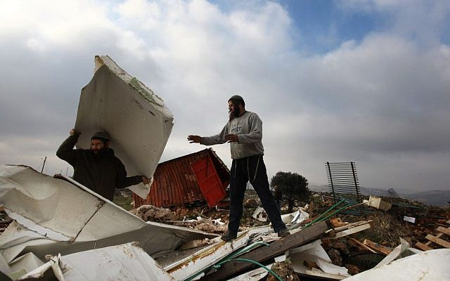 Settlers clean up after a home demolition in the illegal outpost of Mitzpeh Yitzhar, near Yitzhar, in 2011. (photo credit: Kobi Gideon / Flash90.)