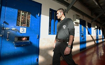 A guard is seen in an Israeli prison holding Palestinian prisoners (Moshe Shai/Flash90/File)