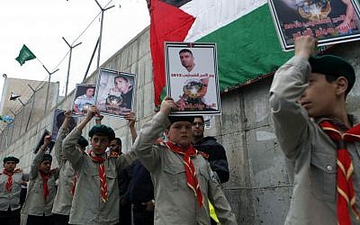 Palestinian youth hold placards during a solidarity rally for Palestinian prisoners in Israeli jails, organized by Hamas, in the Shuafat refugee camp, Jerusalem on April 19, 2013. (photo credit: Sliman Khader/Flash90)