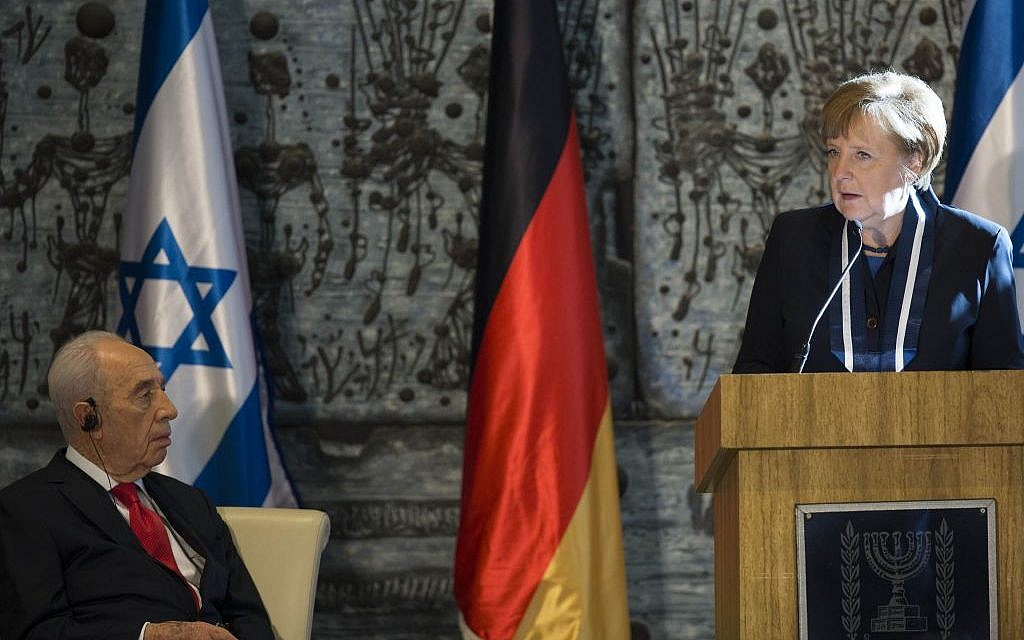 President Shimon Peres listens to German Chancellor Angela Merkel at the president's residence in Jerusalem, February 25, 2014. (Photo credit: Yonatan Sindel/Flash90)
