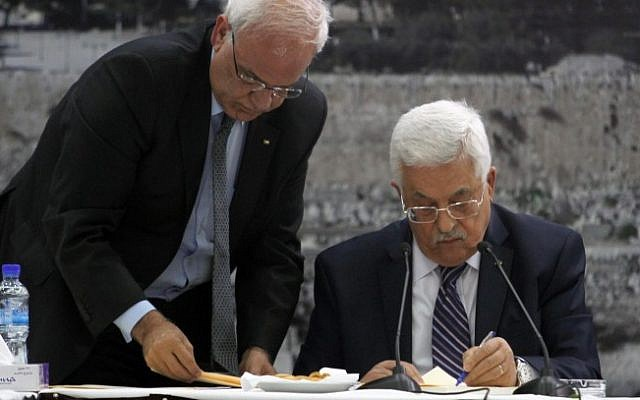 Palestinian Authority President Mahmoud Abbas, right, signs a request to join 15 United Nations-linked and other international treaties at his headquarters in the West Bank city of Ramallah on Tuesday, April 1, 2014. Standing next to him is Saeb Erekat. (Issam Rimawi/Flash90)