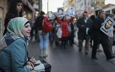 A Muslim woman sitting on a bench watches as Israeli demonstrators carry signs and pictures of victims of terror at a march against the release of Palestinian prisoners on April 2, 2014. The demonstration began at Cafe Ne'eman, which was the site of a suicide bombing at the Sbarro restaurant, and from there down Jaffa road, along other sites of past attacks. (photo credit: Hadas Parush/Flash90)