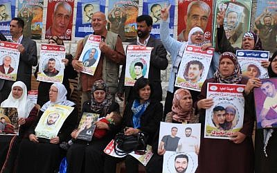 Palestinians take part in a protest demanding the release of their relatives held in Israeli jails, in front of the Red Cross office in the West Bank city of Ramallah, on April 15, 2014. (Photo credit: Issam Rimawi/FLASH90)
