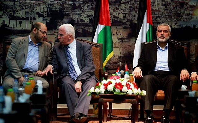 Senior Hamas leader Moussa Abu Marzouk (L) and Azzam Al-Ahmed, a senior Fatah official talk during their meeting in Gaza City on April 22, 2014. At right is Hamas Prime Minister Ismail Haniyeh. (photo credit: Abed Rahim Khatib/Flash90)