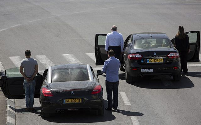 Israelis stand next to their cars at the entrance to the city of Jerusalem, as a two minute siren marking Holocaust Remembrance Day is sounded across Israel, April 28, 2014. (photo credit: Yonatan Sindel/Flash90)