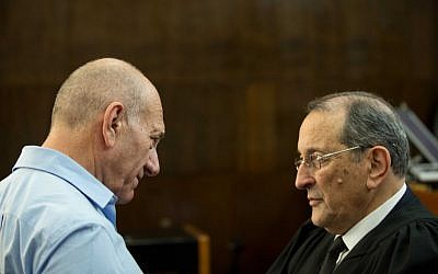 Former prime minister Ehud Olmert speaks with his attorney Eli Zohar in the courtroom of the District Court in Tel Aviv during the sentencing hearings in the Holyland trial on April 29, 2014.  (photo credit: Ben Kelmer/POOL/Flash90)