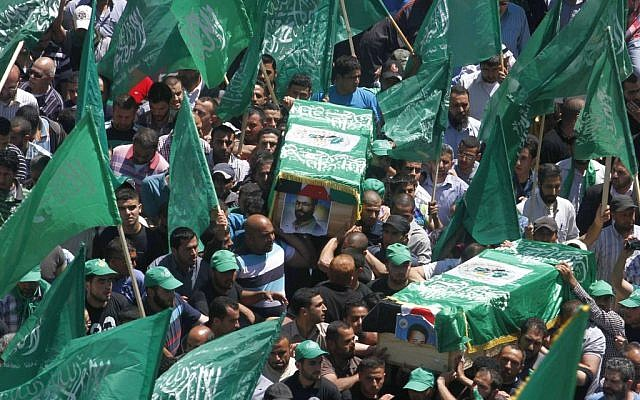Palestinian mourners wave the green flag of the Islamist movement Hamas as they attend the funeral of two Hamas members, Adel and Imad Awadallah, killed by Israeli forces in 1998, after Israel returned the remains of Palestinian militants to their families for burial, on April 30, 2014. (photo credit: Issam Rimawi/FLASH90)