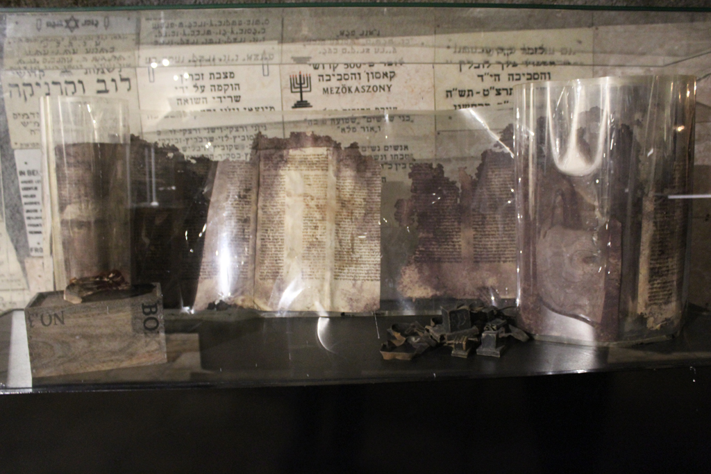 An old Torah, said to be covered with the blood of the rabbi it was wrapped around before he was stabbed to death, stands in the Chamber of the Holocaust. (Photo credit: Rebecca McKinsey/Times of Israel)