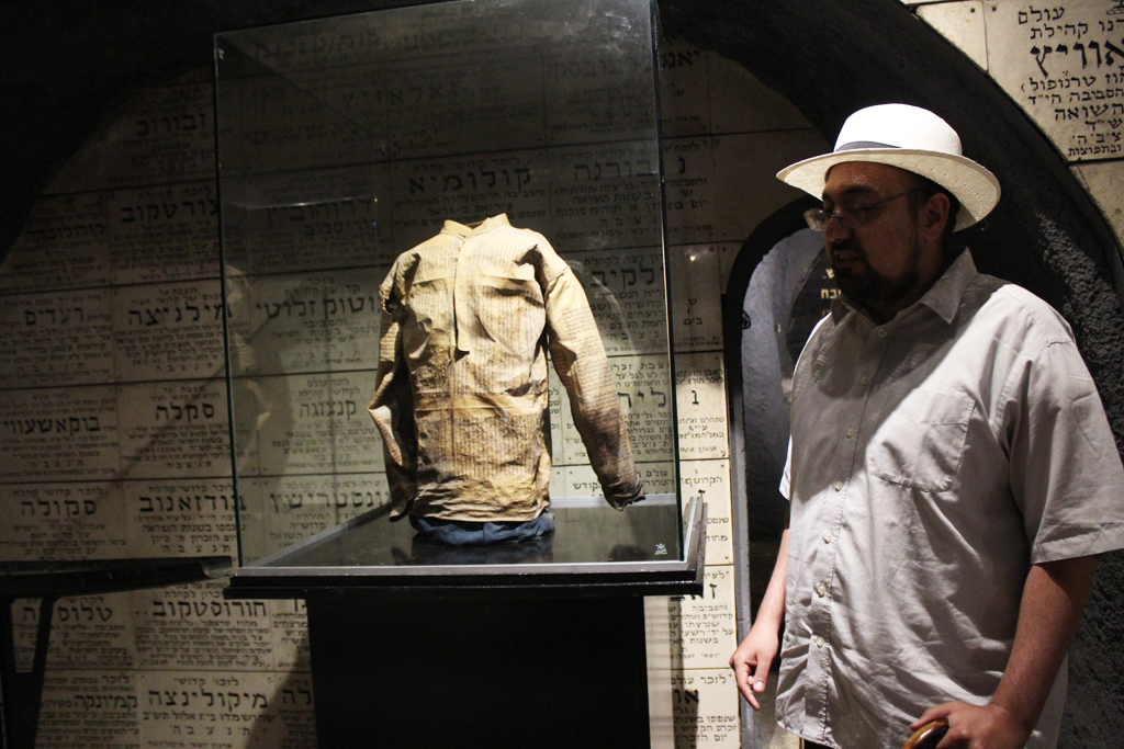 Ilan Goodman, curator at the Chamber of the Holocaust, discusses one of the museum's most important items, a jacket commissioned by a Nazi soldier that was made from pages of the Torah detailing the 98 Curses. (Photo credit: Rebecca McKinsey/Times of Israel)
