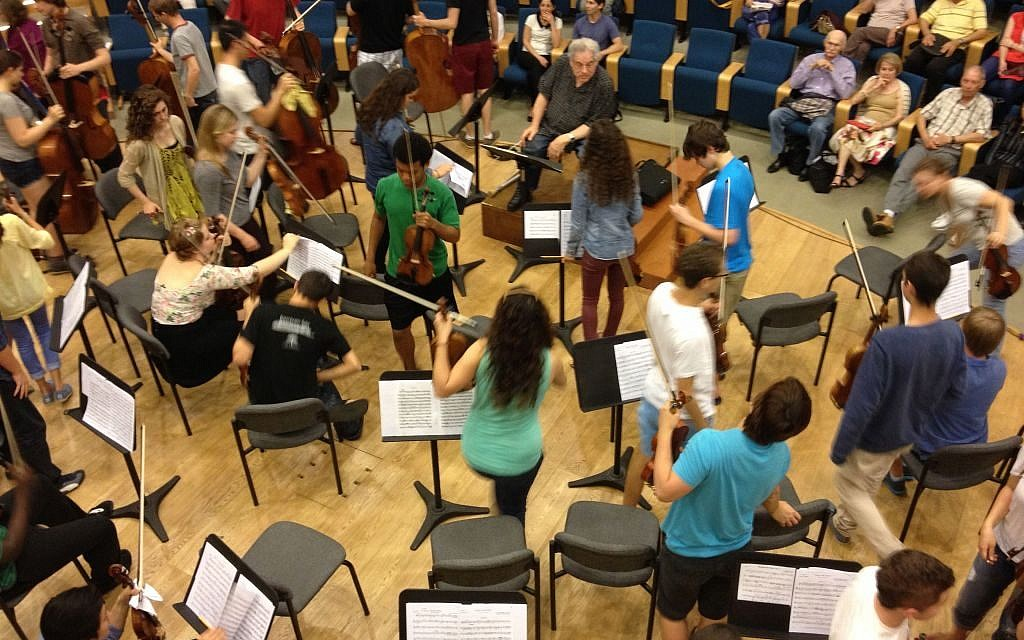 Violinist and conductor Itzhak Perlman tells his students to switch places in order to play a piece of Mozart (photo credit: Jessica Steinberg/Times of Israel)