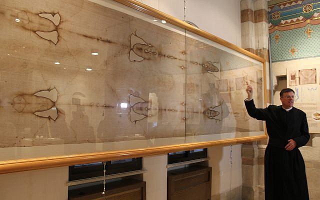 Father Eamon Kelly discusses a full-size replica of the Shroud of Turin (photo credit: Rebecca McKinsey/Times of Israel)