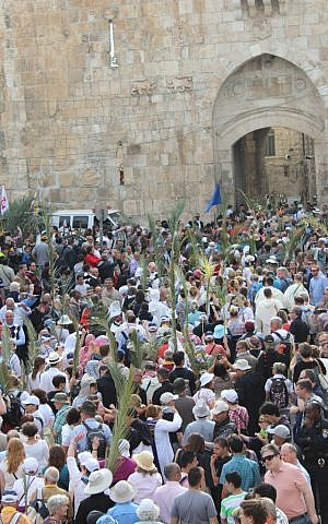 As Holy Week begins, a crowd of people carries palm fronds down from the Mount of Olives into the  Old City to commemorate Jesus' entry into Jerusalem a week before his crucifixion. (photo credit: Rebecca McKinsey/The Times of Israel)