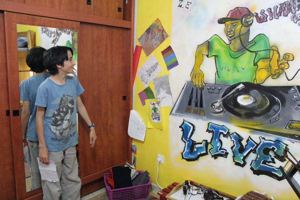 Inbar Elnatan, 12, shares a room with his older brother, Rotem. The walls are covered with a mural their father painted that plays to Rotem's love of DJing, as well as pictures Inbar has drawn. (The Times of Israel/Rebecca McKinsey)