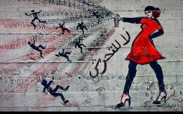 """Graffiti of a woman with the words """"no harassment"""" in Arabic from 2012. (photo credit: AP Photo/Maya Alleruzzo)"""