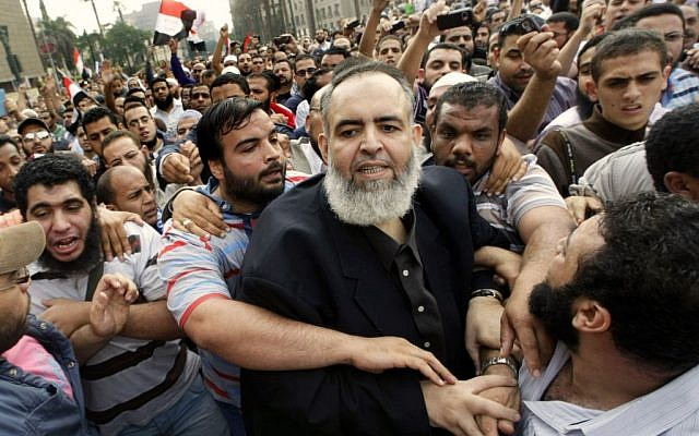 Egyptian Muslim cleric and candidate for the Egyptian presidency Hazem Salah Abu-Ismail, center, is guarded by his supporters as he enters Tahrir Square during a protest against the ruling military council, in Cairo, Egypt,Oct. 28, 2011. (photo credit: AP/Amr Nabil)
