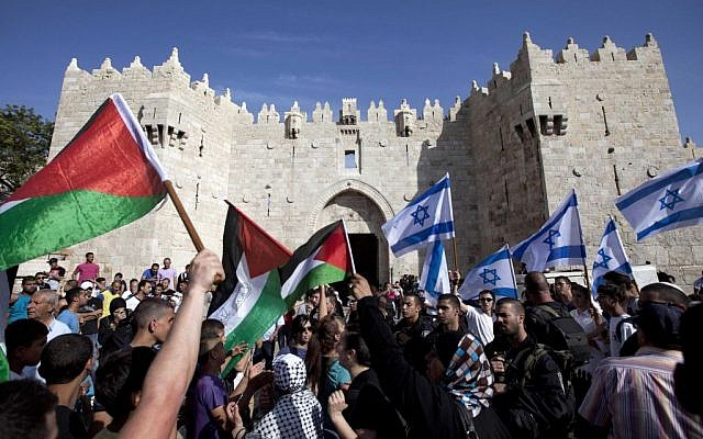 Israelis and Palestinians wave flags as Israelis march in celebration of Jerusalem Day outside Damascus Gate in Jerusalem's Old City, on May 8, 2013. (photo credit: AP/Sebastian Scheiner, File)