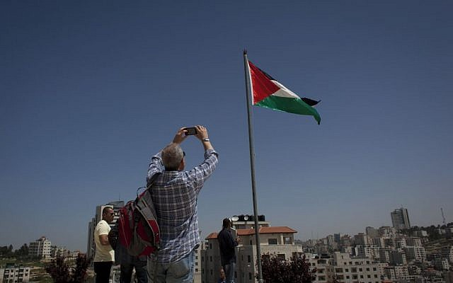 A member of the Israeli and foreigner's group tour to Ramallah takes a photo of the Palestinian national flag during their visit to a museum dedicated to national poet Mahmoud Darwish. (photo credit: AP/Nasser Nasser)