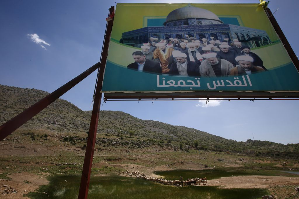 "In this picture taken on Wednesday, April 16, 2014, a Lebanese shepherd, bottom center, herds his flock under a giant poster that shows Sunni and Shiite leading sheikhs gather in front of an image of the al-Aqsa Mosque with the Arabic words reading:""Jerusalem unite us,"" near the barbed wire that separates Lebanon and Israeli-occupied Shebaa farms, southeast Lebanon. (photo credit: AP/Hussein Malla)"