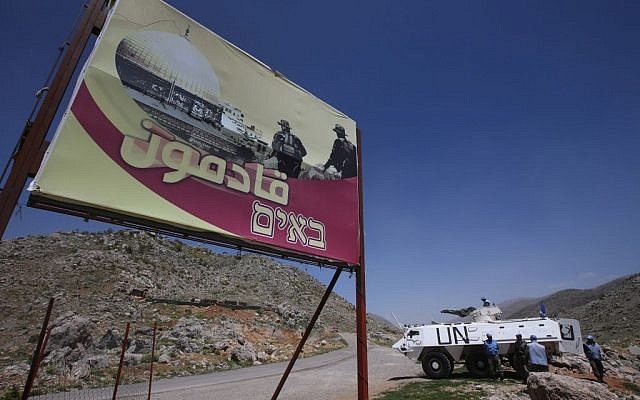 "Indian UN peacekeepers with their armored personnel carrier, right, stand guard next to a giant poster that shows Hezbollah fighters and the Al Aqsa Mosque with Arabic and Hebrew words reading: ""We are coming,"" near the barbed wire that separates Lebanon from the Shebaa Farms. April 16, 2014. AP/Hussein Malla)"