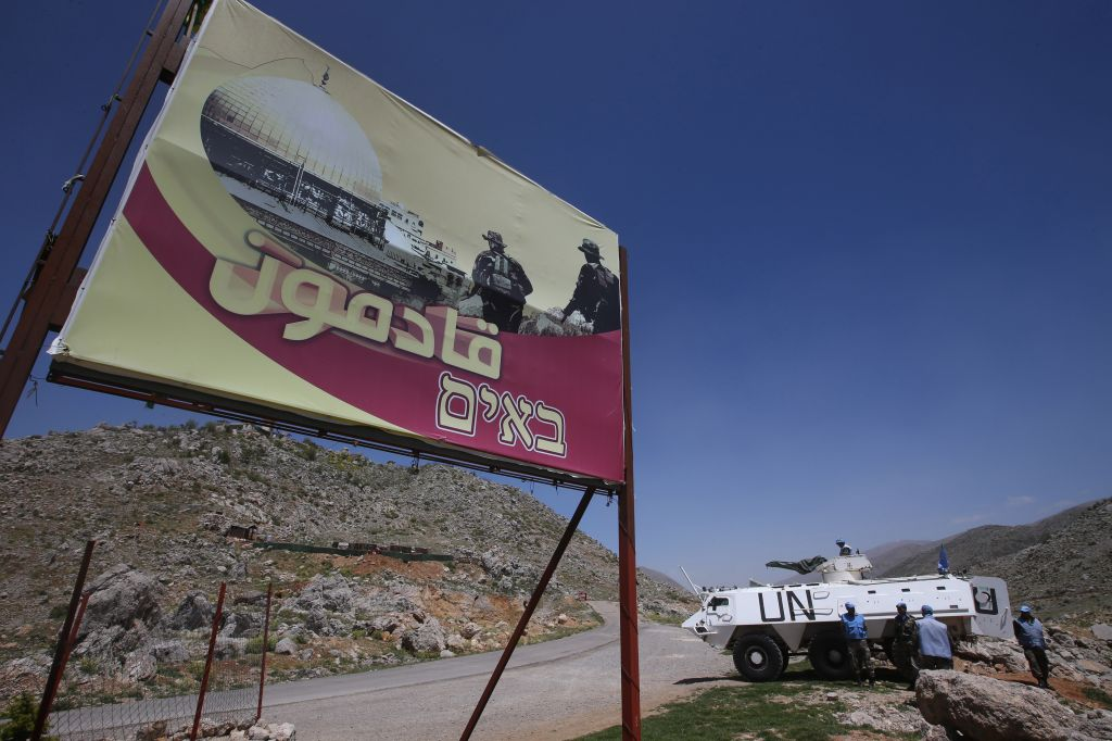 "In this picture taken on Wednesday, April 16, 2014, Indian UN peacekeepers with their armored personnel carrier, right, stand guard next to a giant poster that shows Hezbollah fighters and the Al Aqsa Mosque with Arabic and Hebrew words reading: ""We are coming,"" near the barbed wire that separate Lebanon and Israeli-occupied Shebaa farms, southeast Lebanon. (photo credit: AP/Hussein Malla)"