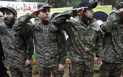 Hezbollah fighters salute during the funeral procession of Hassan al-Laqis, a senior commander of Hezbollah, who was gunned down at his hometown in Baalbek, Lebanon, on December 4, 2013, (photo credit: AP/Hussein Malla)