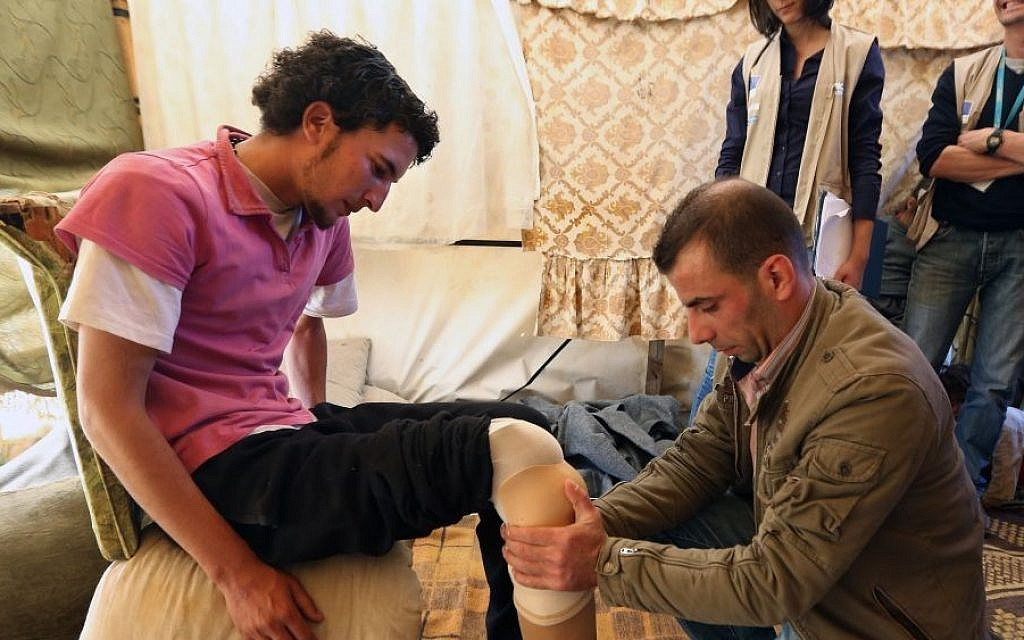 Mustafa Ahmad, left, a 19-year-old who lost his leg in November 2011, is fitted with a prosthetic leg by a Lebanese prosthetic limb maker, right,  March 27, 2014 (photo credit: AP Photo/Bilal Hussein)