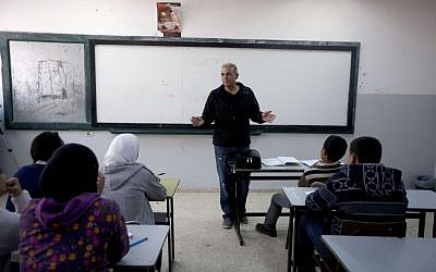 Palestinian Esmat Mansour, a former prisoner who was released after 20 years in Israeli jail, teaches Hebrew to students at a school in the village of Taybeh, near the West Bank city of Ramallah, April 3, 2014. AP/Majdi Mohammed)