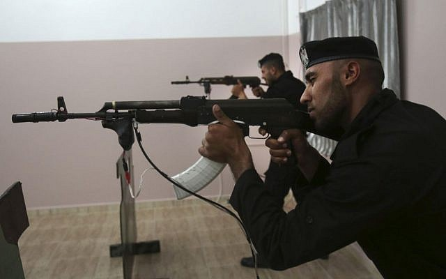 Palestinian security officers Ahed Abu Shabban, 23, foreground, and Muhmmad Debo, 22, aim electronically-modified AK-47 rifles at the headquarters of the security training department of the Hamas interior ministry in Gaza City, in the northern Gaza Strip on Thursday, April 10, 2014.  (photo credit: AP Photo/Adel Hana)