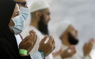 Egyptian Muslim pilgrims, some wearing masks as a precaution against the Middle East respiratory syndrome, pray during the hajj, in Mina near the Muslim holy city of Mecca, Saudi Arabia in 2013.  (photo credit: AP/Amr Nabil, File)