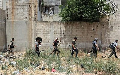 Syrian rebels holding their weapons as they prepare to fight against Syrian troops, in Homs province, Syria, June 18, 2012 . (photo credit: AP/Rebels Battalion of Baba Amro)