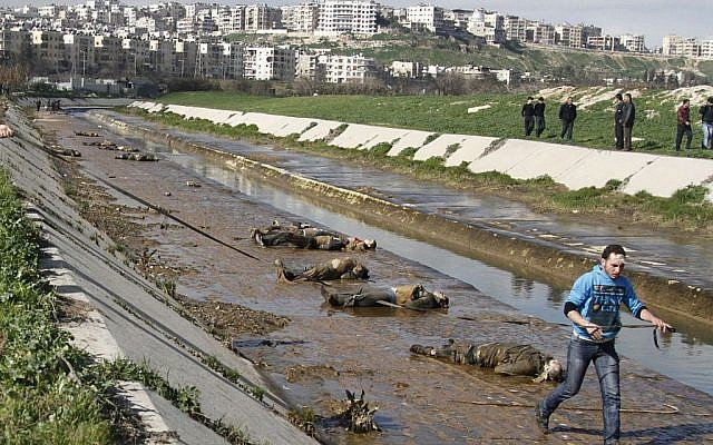 In this January 29, 2013, file photo, a man walks past dead bodies in front of a river in the neighborhood of Bustan al-Qasr in Aleppo, Syria. (photo credit:  AP/Abdullah al-Yassin/File)