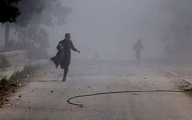 Syrian residents running in the street after a government warplane dropped barrel bombs on the al-Sakhour neighborhood of Aleppo, Syria, on Saturday, April 5, 2014. (photo credit: AP/Aleppo Media Center, AMC/File)