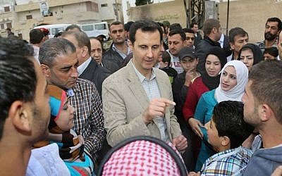In this photo taken on Sunday, April 20, 2014 and released by the Syrian official news agency SANA, Syrian President Bashar Assad, center, speaks with Syrian citizens during his visit to Ain al-Tineh village, near Damascus, Syria. (photo credit: AP/SANA)