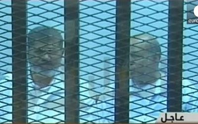 Ousted Egyptian president Mohammed Morsi, left, during his trial in Cairo, Egypt, 2014. (screen capture: YouTube/euronews)