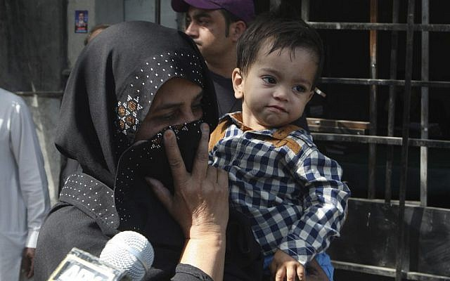 An unidentified family member holds a nine-month-old boy, trying to avoid media as they leave after the boy's court appearance in Lahore, Pakistan, Saturday, April 12, 2014 (photo credit: AP/K.M. Chaudary)