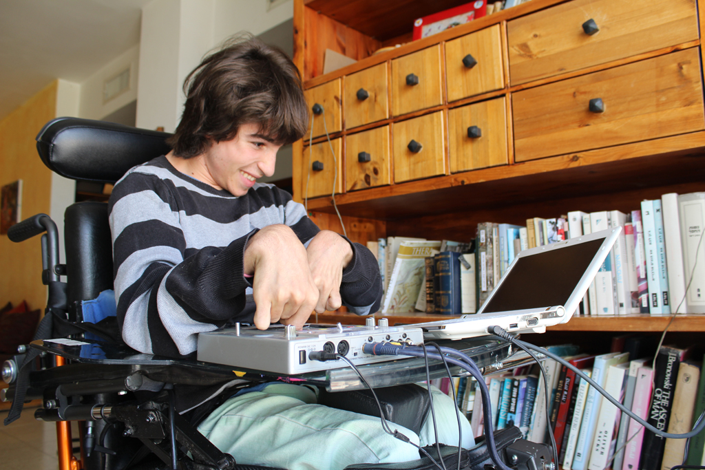 Rotem Elnatan, 19 — the inspiration for Debby Elnatan's product, the Upsee — spins tunes in his home. The teenager enjoys DJing at school parties. (The Times of Israel/Rebecca McKinsey)
