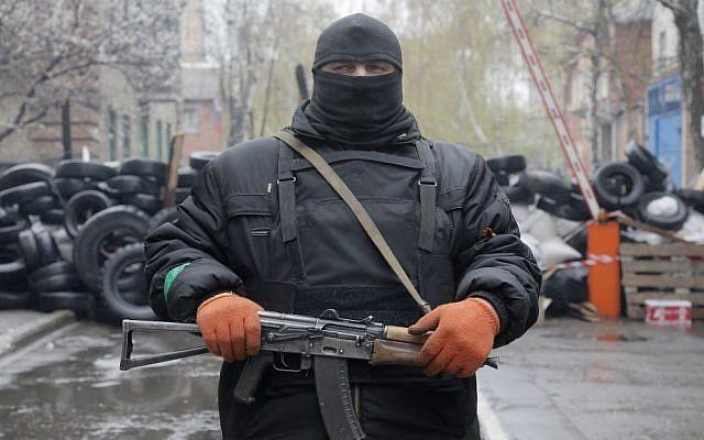 A pro-Russian gunman stands guard at a seized police station in the eastern Ukraine town of Slovyansk on Sunday, April 13, 2014. (photo credit: AP/Efrem Lukatsky)