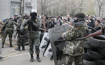 Armed pro-Russian activists occupy the police station carrying riot shields as people watch on, in the eastern Ukraine town of Slovyansk on Saturday, April 12, 2014. Pro-Moscow protesters have seized a number of government buildings in the east over the past week, undermining the authority of the interim government in the capital, Kiev. (photo credit: AP/Efrem Lukatsky)