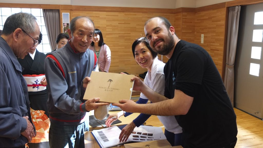 A tsunami survivor is gifted his DVD following his Voices of Tohoku interview. (photo credit: courtesy IsraAid)