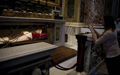 A woman takes pictures of the tomb of Pope John XXIII in St. Peter's Basilica at the Vatican, Thursday, April 24, 2014. Hundreds of thousands of pilgrims and faithful are expected to reach Rome to attend the scheduled April 27 ceremony at the Vatican in which Pope Francis will elevate in a solemn ceremony John XXIII and John Paul II to sainthood. (photo credit: AP Photo/Alessandra Tarantino)
