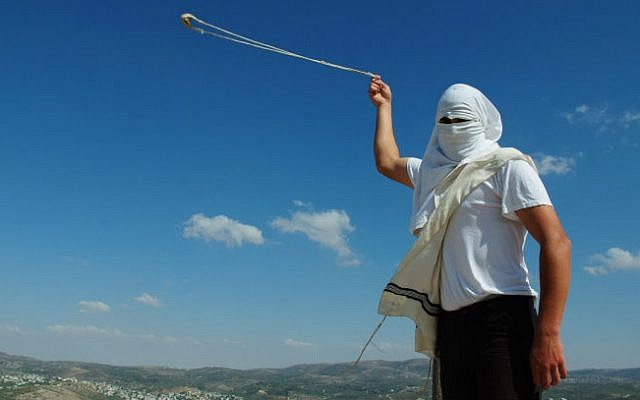 FILE: A masked Jewish settler swings a slingshot as he stands near the West Bank Jewish settlement of Yitzhar, on May 19, 2013. (Mendy Hechtman/Flash90)