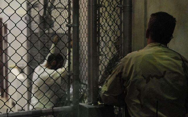 Illustrative: A sailor stands watch over a cell block in Guantanamo Bay's detention facility while detainees look through magazines and books, on March 30, 2010. (Joshua Nistas/US Navy/Department of Defense)