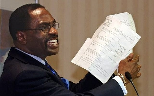 "In this Jan. 29, 2004 file photo, former boxer, Rubin, ""Hurricane"" Carter, holds up the writ of habeas corpus that freed him from prison, during a news conference held in Sacramento, Calif. (photo credit: AP Photo/Rich Pedroncelli, File)"